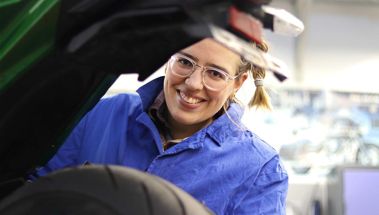 Lisa Schmidla in der Werkstatt, schaut hinter Motorrad hervor