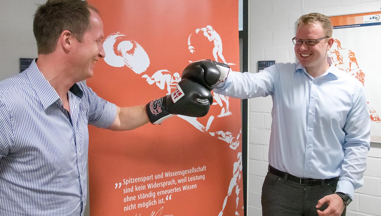 Boxer Max Keller und sein Mentor Roland Mönikes von Advyce klatschen sich mit Boxhandschuhen ab