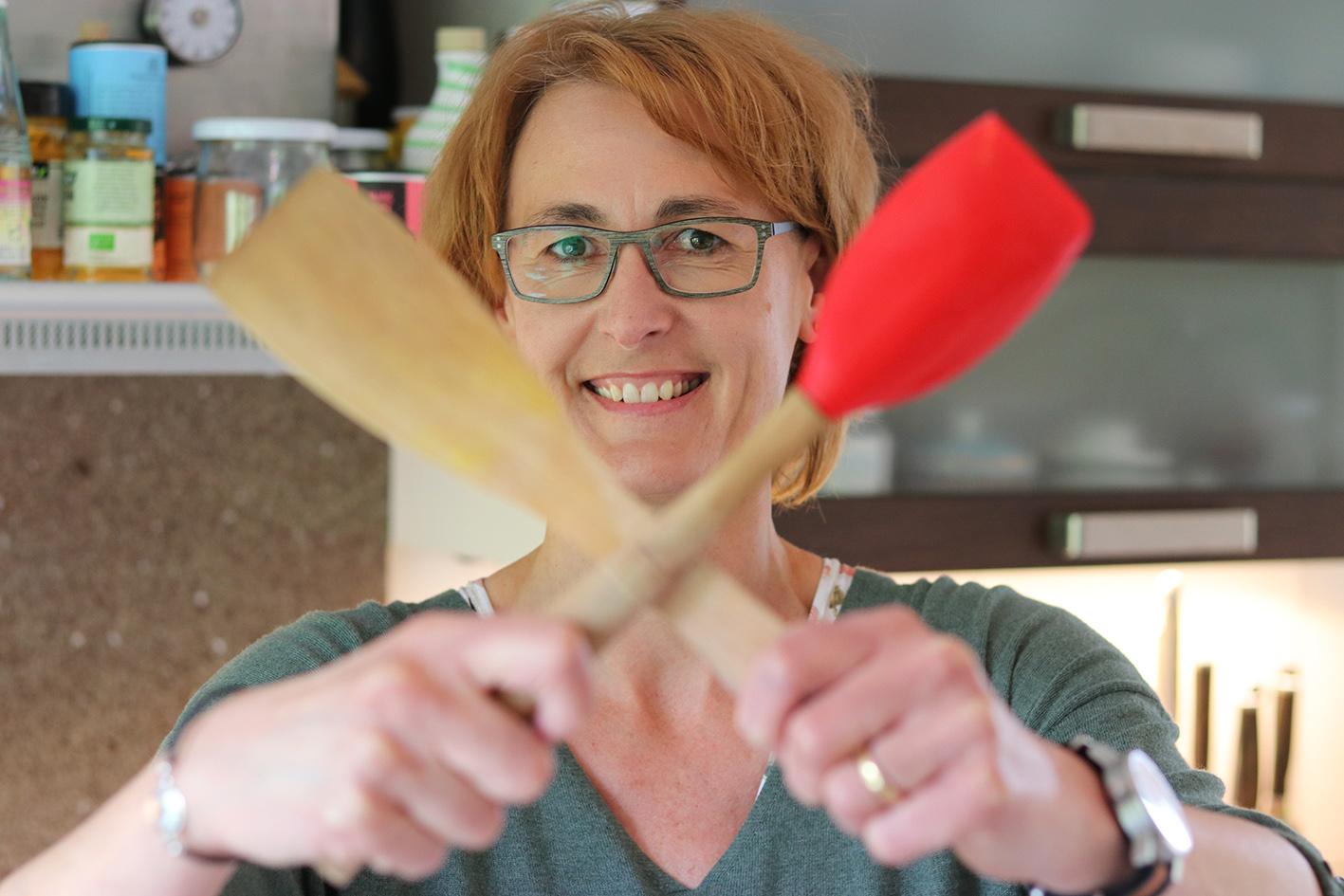 Gundi Goeritz mit gekreuzten Kochlöffeln